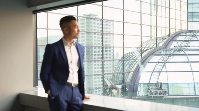 chinese businessman standing by the window - fashionable stock videos & royalty-free footage