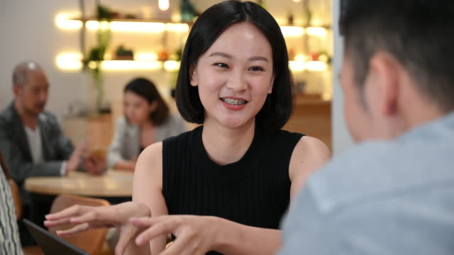 chinese businesswoman in cafe with colleague - solutions stock videos & royalty-free footage