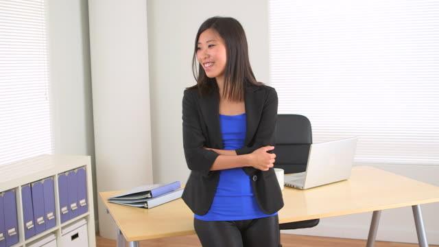 vídeos de stock, filmes e b-roll de chinese businesswoman leaning on desk while talking to colleague - presidente de empresa