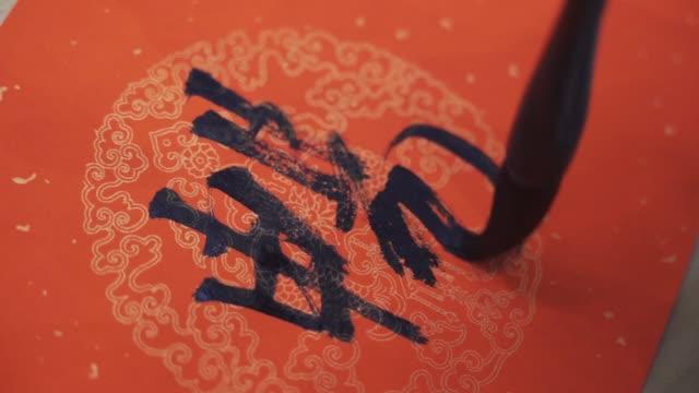 chinesische kalligraphen schreiben frühling festival couplets - kalligraphieren stock-videos und b-roll-filmmaterial