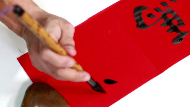 """chinesische kalligrafie gezeigt, dass sie """"yang"""" schreiben auf roten papier - schwarz ethnischer begriff stock-videos und b-roll-filmmaterial"""