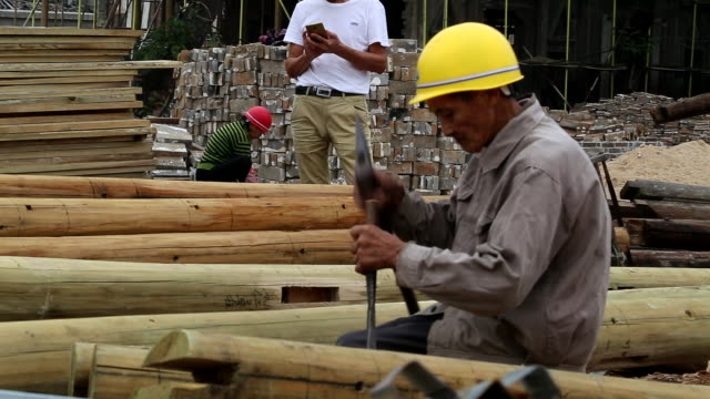 stockvideo's en b-roll-footage met chinese carpenter working for building a traditional wooden house - traditie