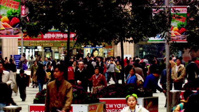 Chinese citizens walk through a crowded plaza.