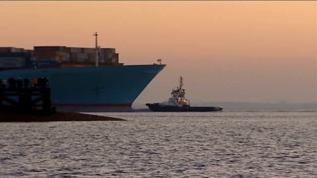 stockvideo's en b-roll-footage met chinese container ship of festive goods docks at felixstowe; suffolk: felixstowe: dusk emma maersk iii being guided into port by tug boat pilot boat... - pilot