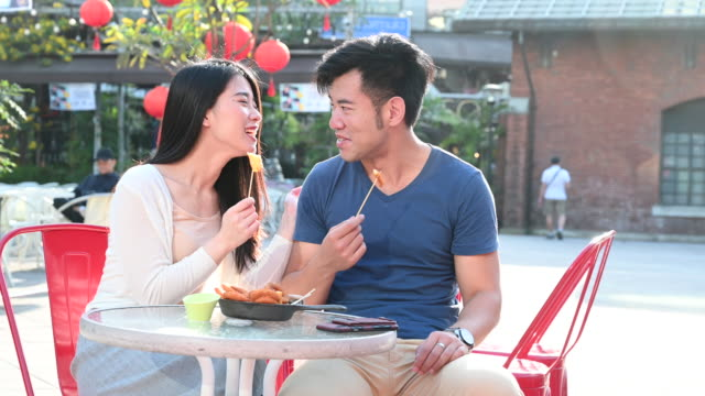 Chinese couple eating snacks and chatting in cafe