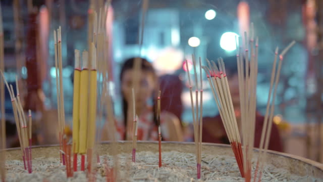 vídeos de stock e filmes b-roll de chinese couple holding light incense stick and candle to pay respect in temple. - incenso