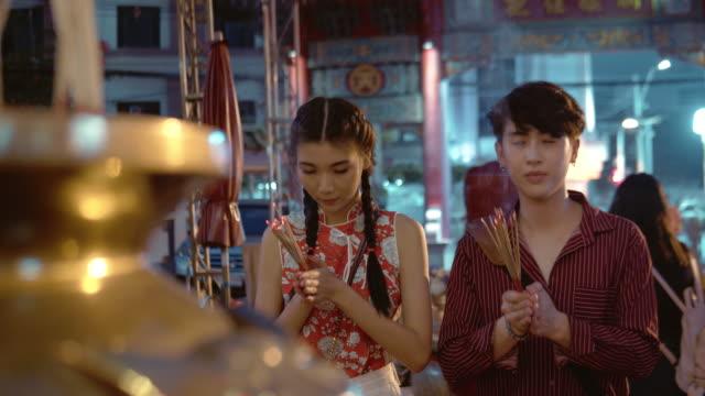 chinesisches ehepaar hält licht weihrauch stick und kerze um respekt im tempel zu zahlen. - chinesische kultur stock-videos und b-roll-filmmaterial