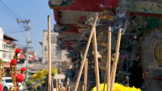 寺院で敬意を払うために光の香とろうそくを持つ中国のカップル。 - 許し点の映像素材/bロール