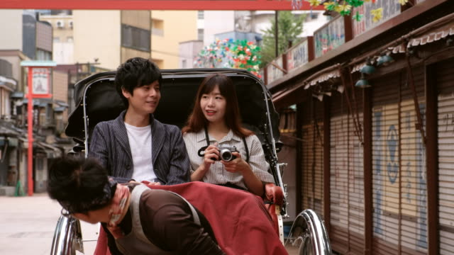 chinese couple on vacation in tokyo japan jinrickshaw - risciò video stock e b–roll