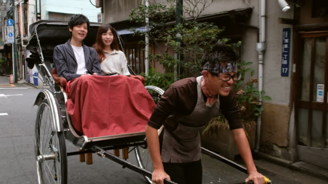 chinese couple on vacation in tokyo japan jinrickshaw - risciò a motore video stock e b–roll