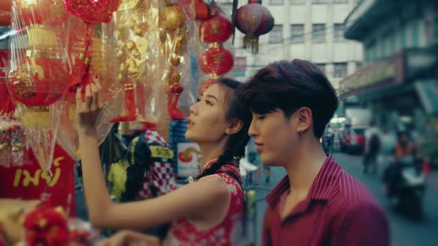 chinesisches ehepaar einkaufen in straßenmarkt. - chinesische kultur stock-videos und b-roll-filmmaterial