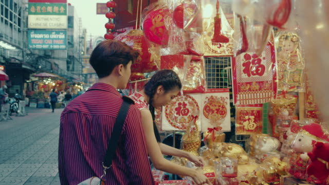 chinese couple shopping in street market. - street market stock videos & royalty-free footage