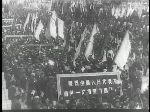 vídeos de stock e filmes b-roll de chinese crowd lifts paper doves and flags over their heads during a huge parade while nikolai bulganin, mao tse tung and nikita khrushchev wave from... - mao tse tung