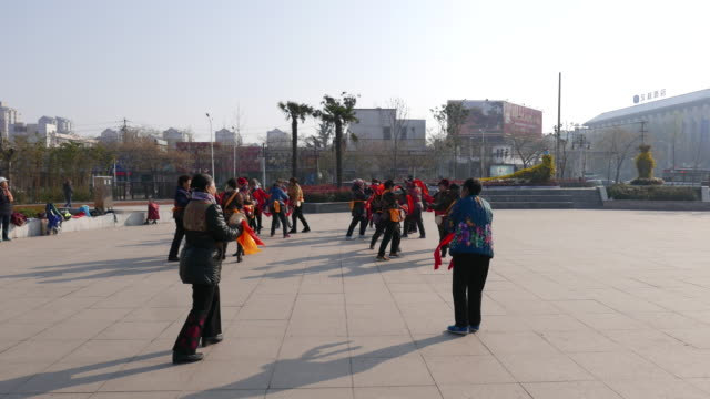 vídeos de stock e filmes b-roll de chinese dama are dancing waist drum in a park square on a morning. according to a report on china's square dancing industry released in 2015, it is... - cintura