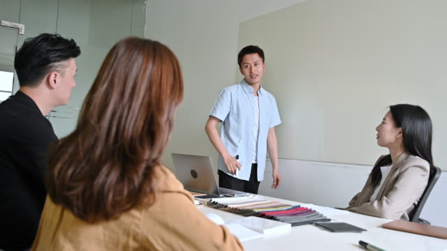chinese designer pitching ideas for project to work colleagues - sales pitch stock videos & royalty-free footage