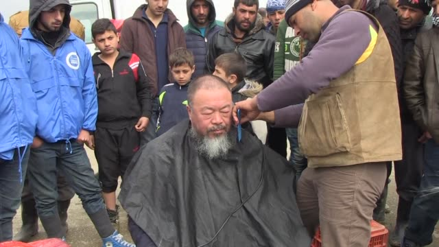 Chinese dissident artist Ai Weiwei gets a haircut from a migrant at the Idomeni border camp