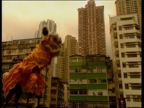 vídeos y material grabado en eventos de stock de chinese dragon dancers with hong kong tower blocks in background - dragon chino