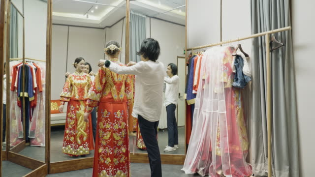 chinesische kleid designer putting finishing touches auf qun gua - glamour stock-videos und b-roll-filmmaterial