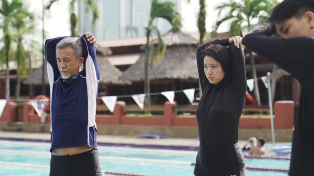 chinese female coach instructor having warming up exercise before getting down to the pool for swimming class - warm up exercise stock videos & royalty-free footage