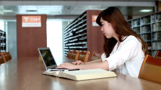 stockvideo's en b-roll-footage met chinese female student using laptop in library,real time. - koreaanse etniciteit