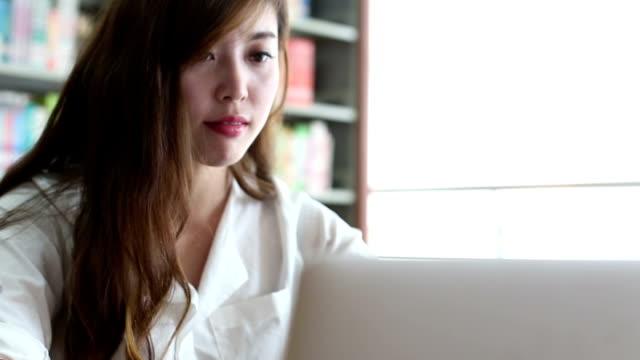 中国の女子学生のラップトップを使用して、ライブラリ、リアルタイム。 - デスクトップ型パソコン点の映像素材/bロール