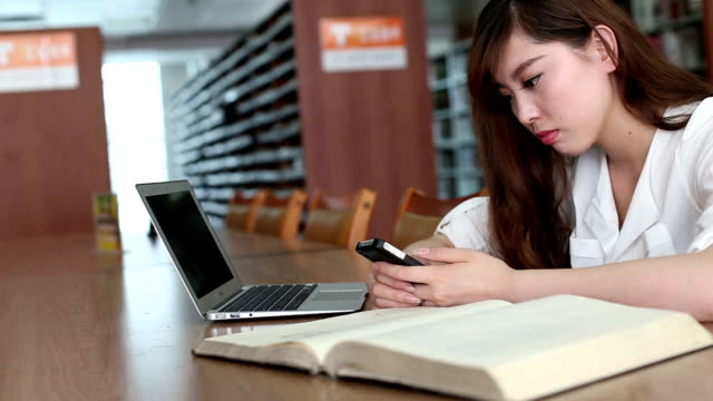 Chinese female student using mobile phone in library,real time.