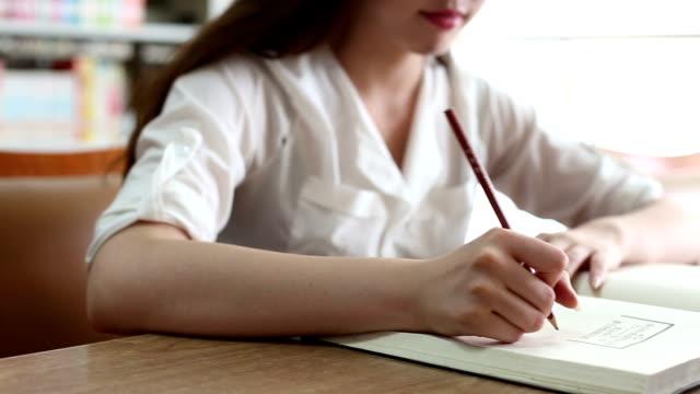 中国の女子学生で執筆ノートライブラリー、リアルタイム。 - 鉛筆点の映像素材/bロール