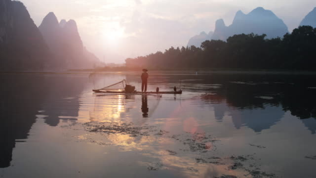 chinese fisherman throwing fishing net at sunrise - chinese ethnicity stock videos & royalty-free footage