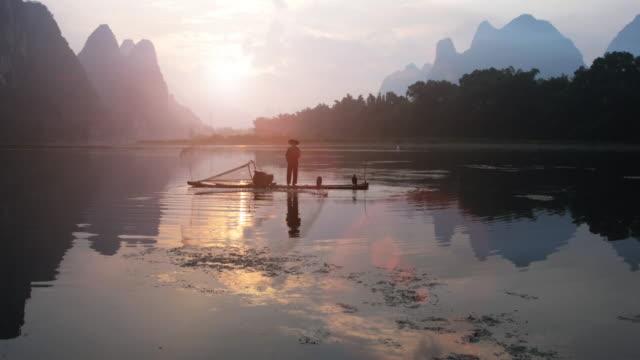Chinese Fisherman throwing fishing net at sunrise