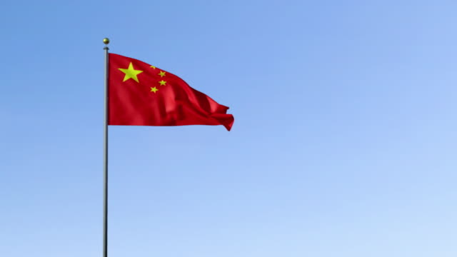 ws, chinese flag blowing against blue background - chinese flag stock videos & royalty-free footage