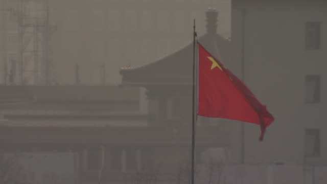 chinese flag flies among a foggy beijing skyline, while a flock of birds soar in the background. - flock of birds stock videos & royalty-free footage