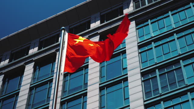 chinese flag in front of a building in shenzhen, china - communism stock videos & royalty-free footage