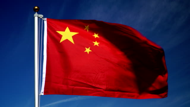 4k: chinese flag on flagpole in front of blue sky outdoors (china) - chinese flag stock videos and b-roll footage