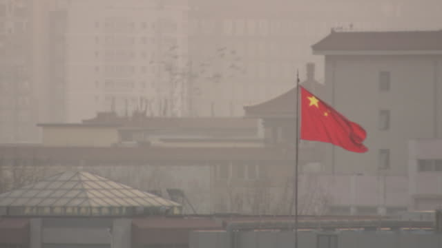 chinese flag waving in the city of beijing, china. - smog stock videos & royalty-free footage