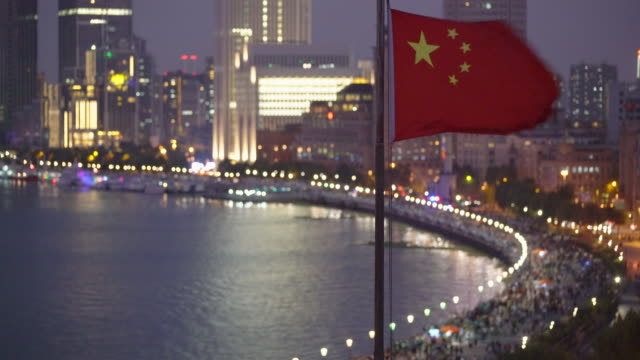 ws chinese flag waving, shanghai skyline in background - chinese flag stock videos and b-roll footage