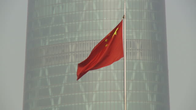 chinese flag with building in guangzhou china - chinese flag stock videos & royalty-free footage