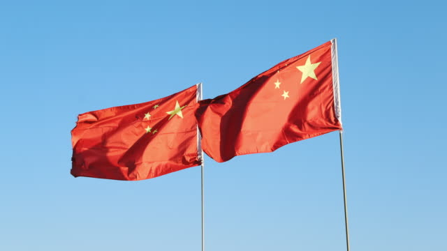 chinese flags blowing in strong wind - chinese flag stock videos and b-roll footage