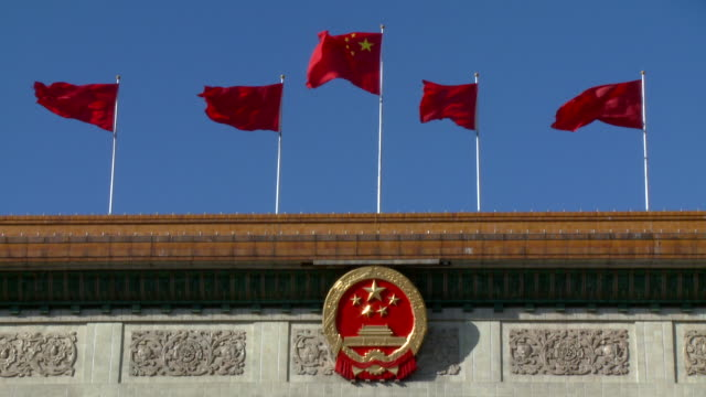 vídeos de stock e filmes b-roll de ms chinese flags flapping on top of the great hall of the people, chinese national emblem hanging in centre, beijing, china - pequim