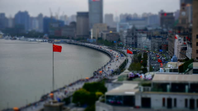 Chinese flags wave above pedestrians and vehicles in Shanghai's Bund district.