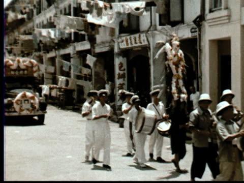 vídeos y material grabado en eventos de stock de 1957 montage chinese funeral procession through street. gongs, drums, umbrellas, mourners, casket in cart / singapore / audio - 1957