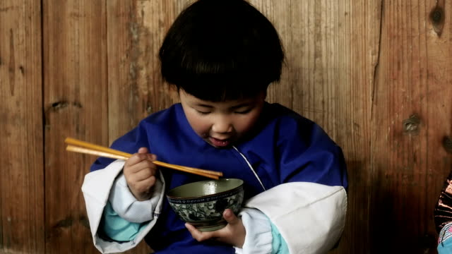 Chinese girl learning to eat with chopsticks from a bowl