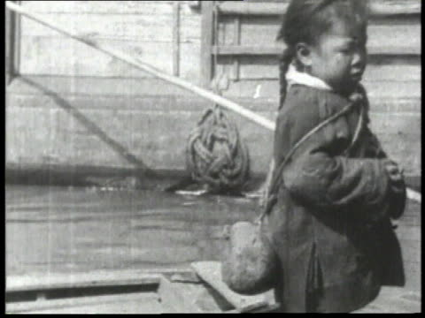 1932 montage chinese girl standing on a boat in the water and a chinese boy looking at the camera with river behind him / china  - 1932 stock videos & royalty-free footage