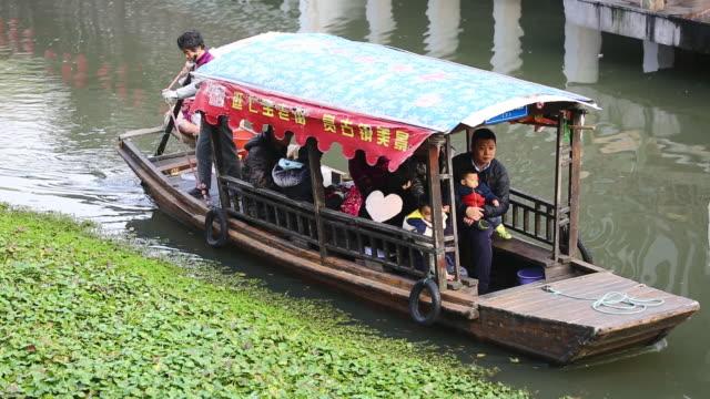 Chinese gondola rowing through Shanghai canal