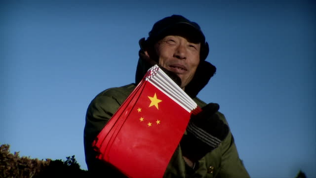 SLO MO CU Chinese guard with bunch of Chinese flags sitting in morning sun and smiling, Beijing, China