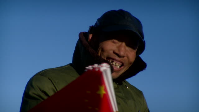 cu chinese guard with bunch of chinese flags sitting in morning sun, beijing, china - cappotto invernale video stock e b–roll