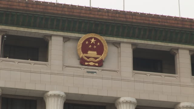 CU Chinese insignia on building/ ZO soldier walking past government building as traffic passes/ Beijing, China