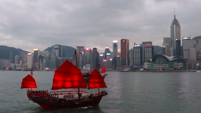 vidéos et rushes de chinese junk boat with hong kong central skyline and victoria harbour at dusk - terre en vue