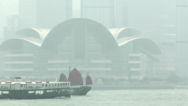 WS Chinese Junk Duk Ling and Star Ferry on foggy day in Victoria Harbor, downtown buildings with Convention and Exhibition Centre in background / Hong Kong, China