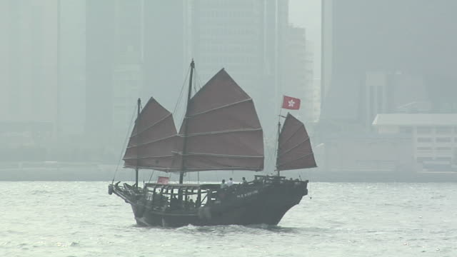 vidéos et rushes de ws chinese junk duk ling on foggy day in victoria harbor, downtown buildings in background / hong kong, china - jonque