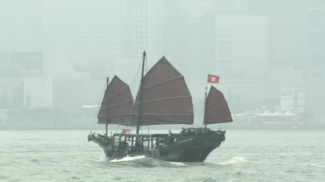 vidéos et rushes de ws pan chinese junk duk ling on foggy day in victoria harbor, downtown buildings in background / hong kong, china - jonque